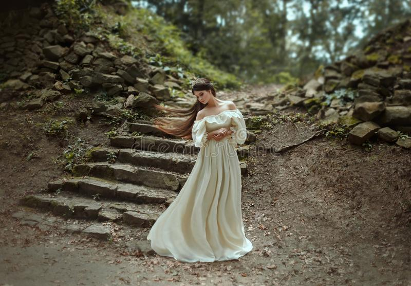 Young princess with very long hair posing against the background of an old stone staircase. The girl has a crystal crown. And a white, flying vintage dress royalty free stock photography