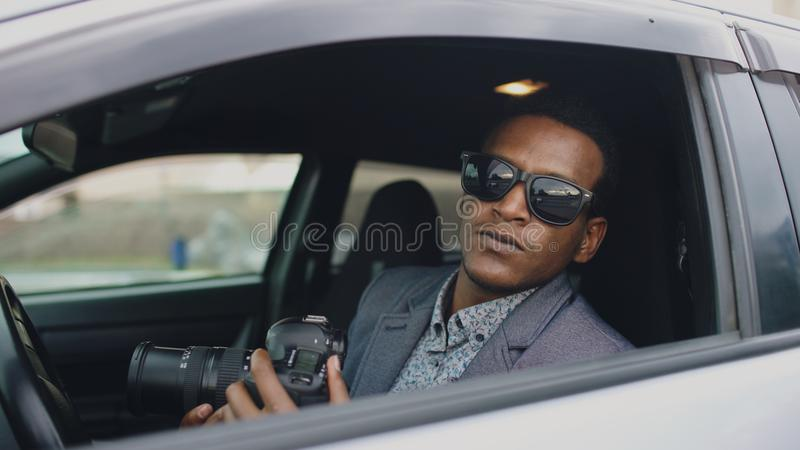 Private detective man sitting inside car and photographing with dslr camera. Young private detective man sitting inside car and photographing with slr camera stock image