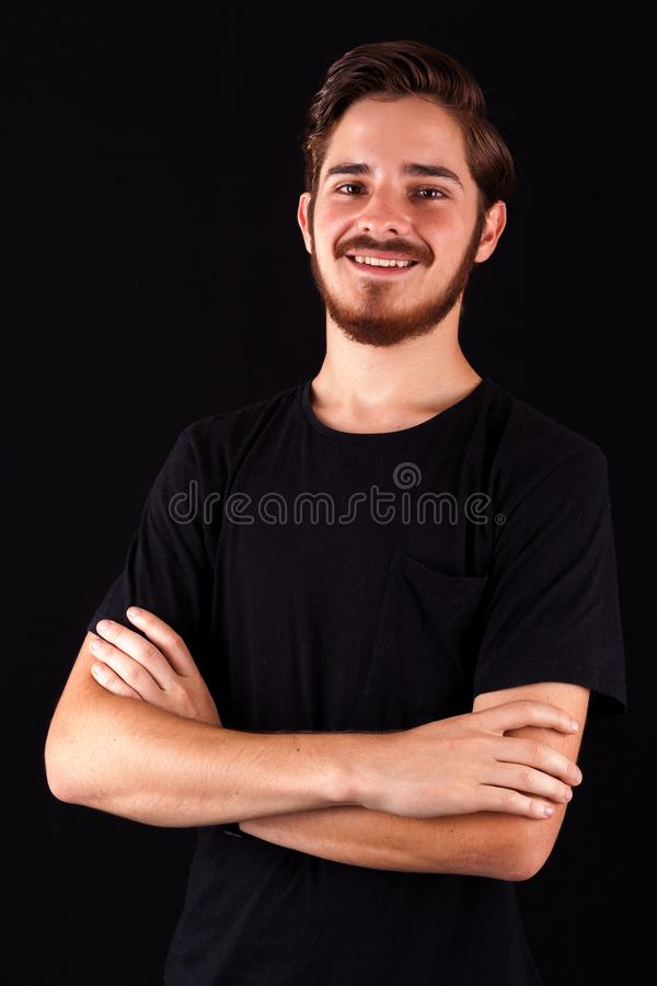 Young professional adult in black tshirt smiling and happy and content. Color expressive dramatic effect, dark and moody series. Studio shoot royalty free stock image