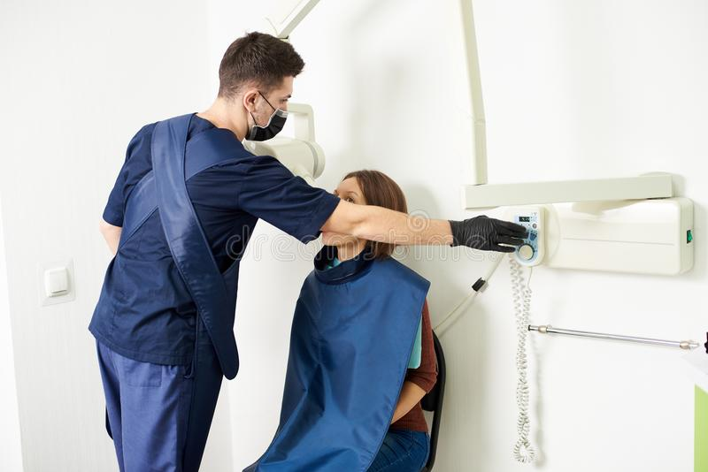 Young professional in a blue uniform is taking care of a female patient in a white dental office stock images