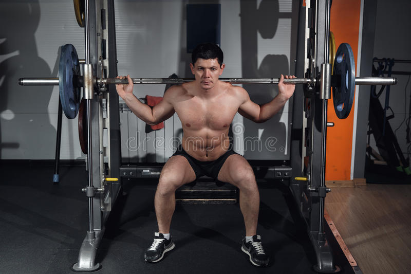 Young professional bodybuilder working out doing squats with barbell. Young professional bodybuilder working out doing squats with barbell stock photos