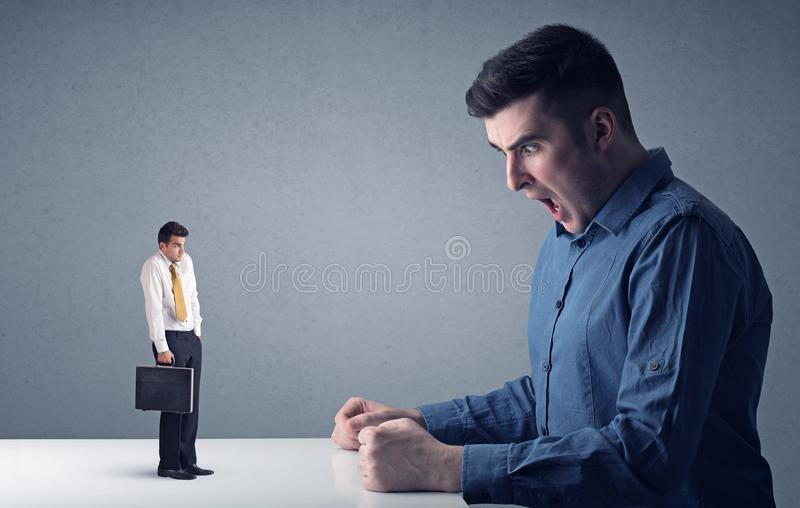 Young businessman fighting with miniature businessman royalty free stock photography