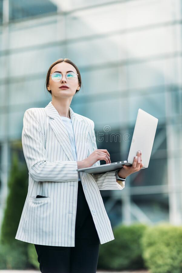 Young professional businesswoman using her laptop outside while working at modern business center stock photography