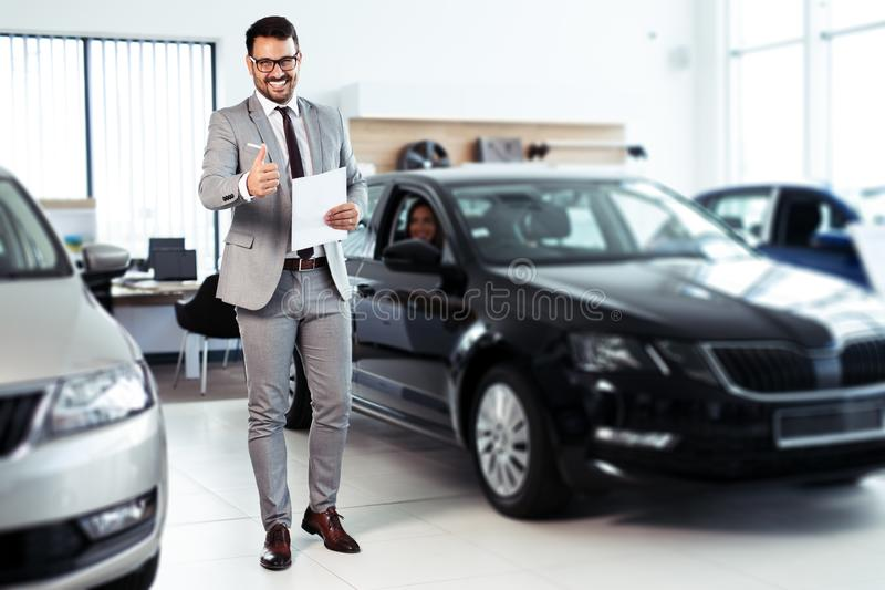 Professional car dealer posing proudly at auto showroom. Young Professional car dealer posing proudly at auto showroom royalty free stock image