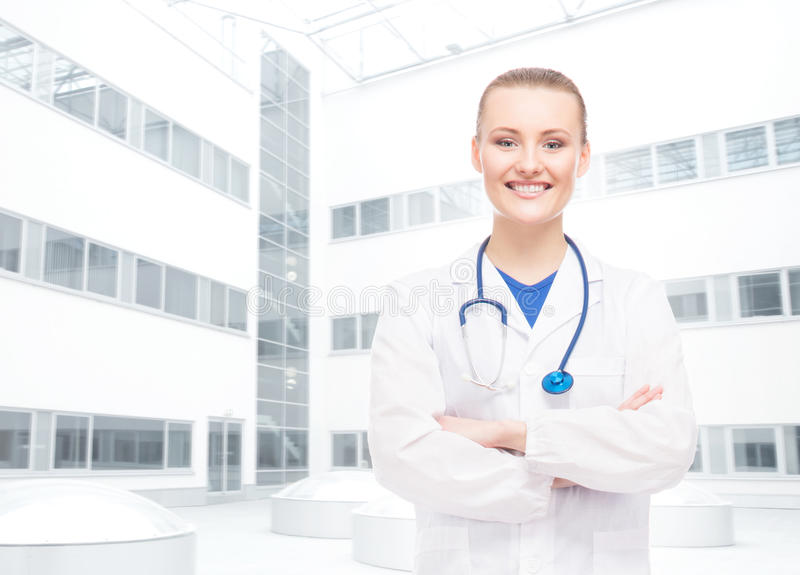 Young, professional and cheerful female doctor in white coat being confident over clinic background. stock images