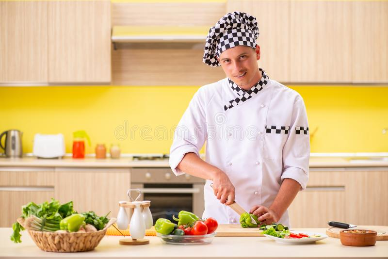 The young professional cook preparing salad at kitchen stock photography