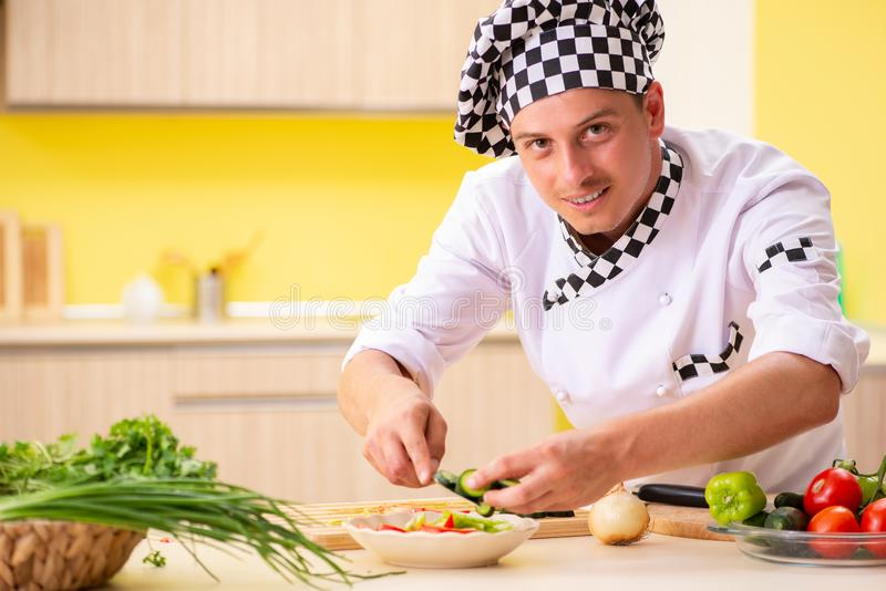 The young professional cook preparing salad at kitchen royalty free stock images