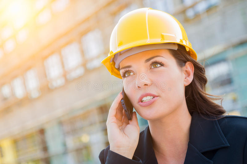 Young Professional Female Contractor Wearing Hard Hat at Contruction Site Using Cell Phone. royalty free stock photography