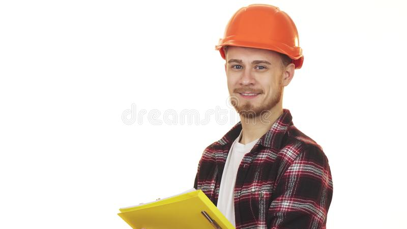 Young professional male contractor in hardhat making notes smiling. Young happy handsome bearded male industry worker wearing hardhat smiling joyfully taking stock images