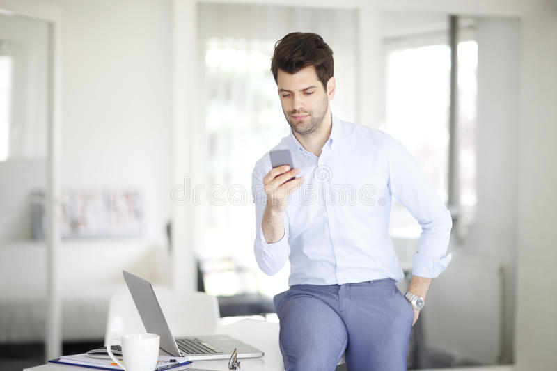 Young professional man with mobile phone. Shot of a businessman texting in his cellphone while sitting at desk in front of laptop royalty free stock photo