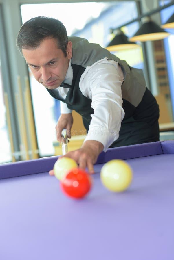 Young professional man playing billiards in dark billiard club stock photo