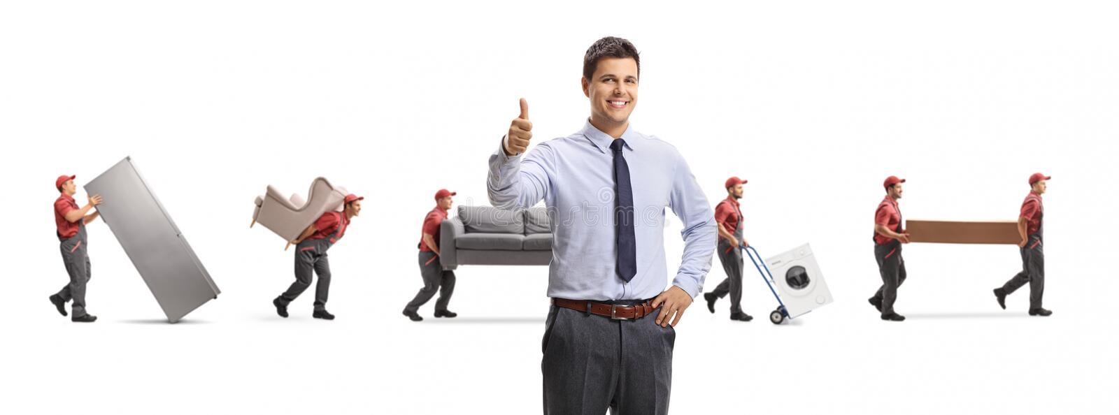 Young professional man showing thumbs up and movers carrying furniture stock photo