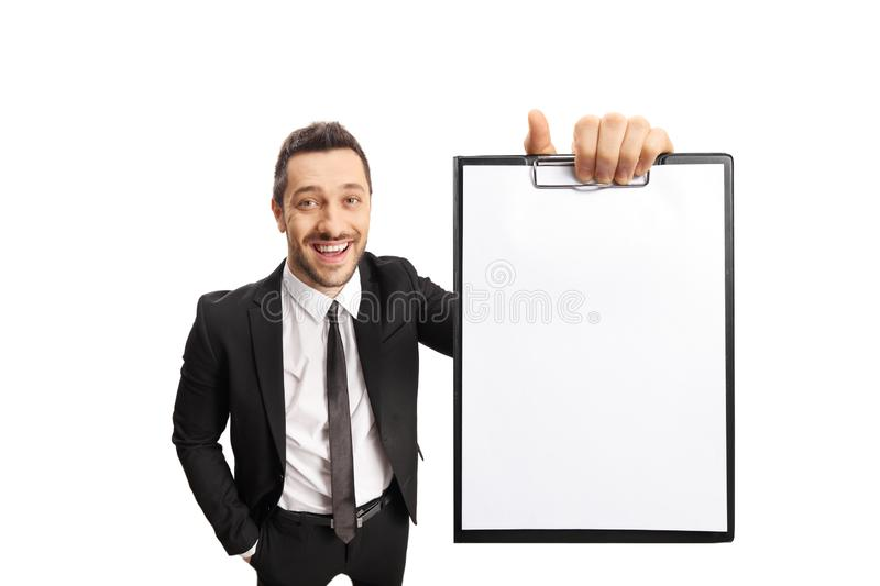 Young professional man in a suit smiling and holding a clipboard royalty free stock photography