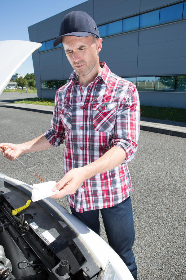 Young professional mechanic checks oil in car royalty free stock images
