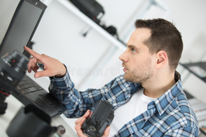 Young professional photographer busy retouching images on laptop stock images
