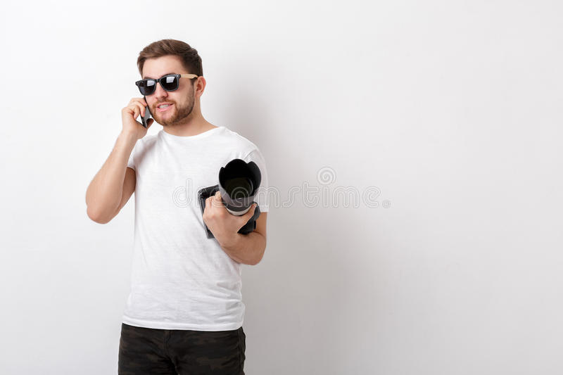 Young professional photographer in white shirt holds digital cam. Young professional photographer in a white shirt holds a heavy digital camera with a long lens stock photo