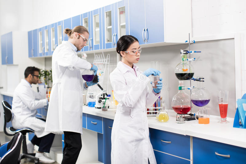 Young professional scientists making experiment in research laboratory. Group of young professional scientists making experiment in research laboratory royalty free stock images
