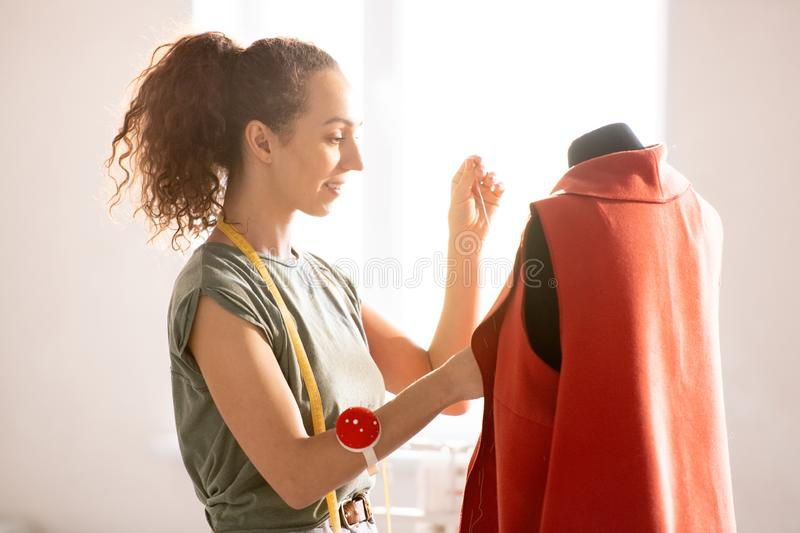 Making coat. Young professional seamstress in casulawear standing by dummy with red unfinished coat on in workshop stock image