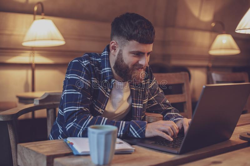 Young professional surfing the Internet on his laptop in a cafe royalty free stock image