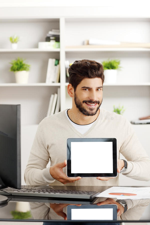 Young professional with tablet. Portrait of young professional sitting at office in front of computer while holding hands digital tablet stock image