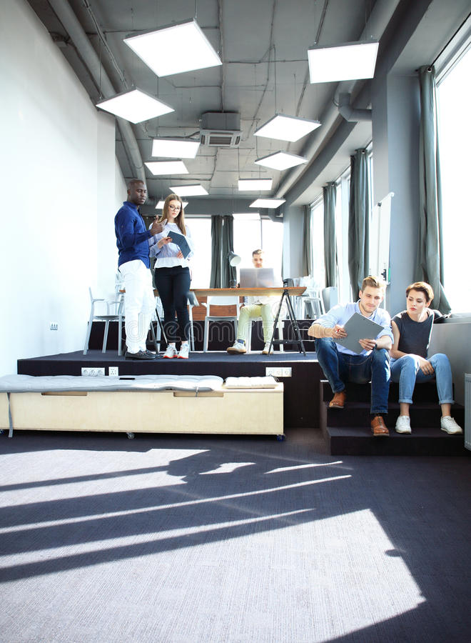 Young professional team. Group of young modern people in smart casual wear standing in the creative office royalty free stock images