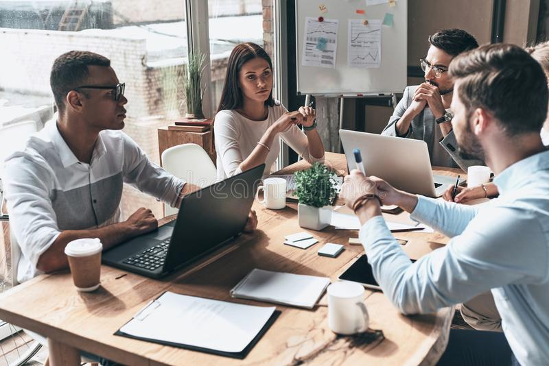 Young professional team. Top view of young modern people in smart casual wear discussing business while working in the creative o stock images