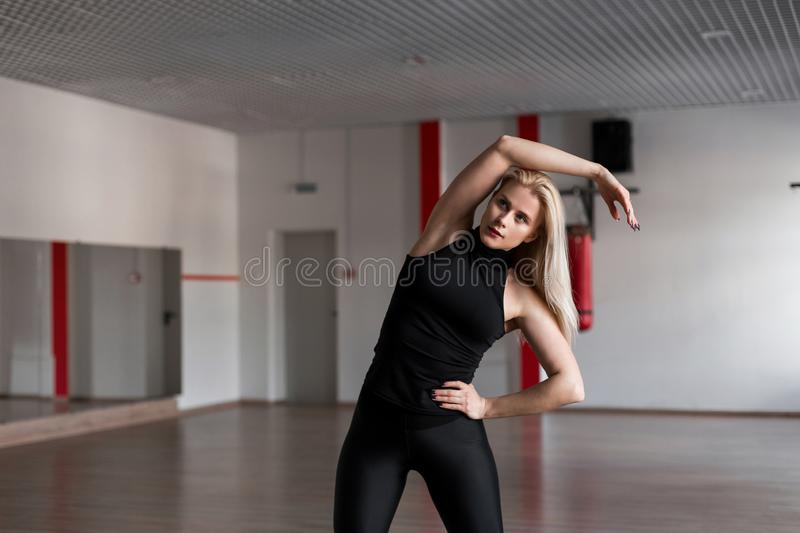 Young professional trainer woman in black sportswear engaged in a fitness studio. Beautiful girl in training in a sport class. royalty free stock image
