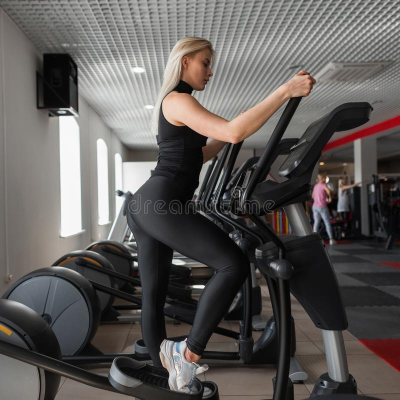 Young professional trainer woman in black sportswear in gym shoes is engaged on a stepper simulator in a fitness studio. stock images