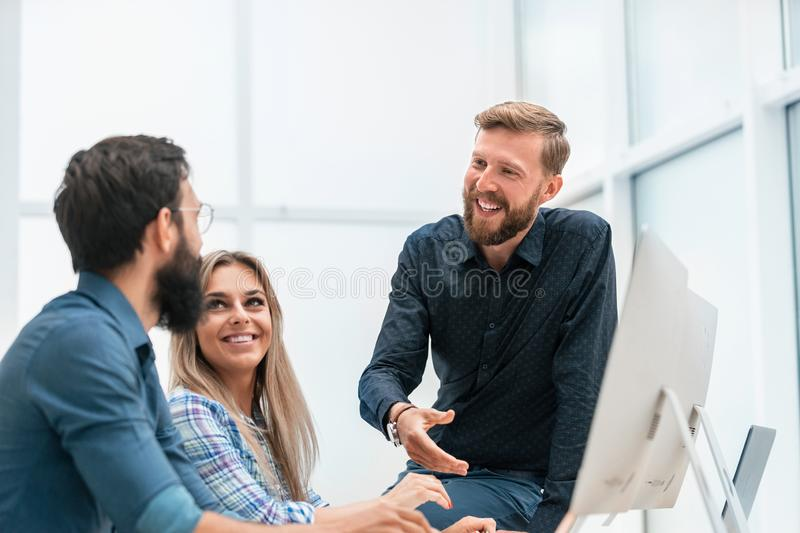 Young professionals shaking hands in the workplace. The concept of teamwork stock image