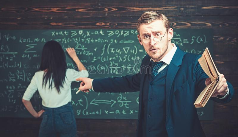 Young professor pointing at the board while holding book in straight hand. Young teacher giving explanations to students stock photo
