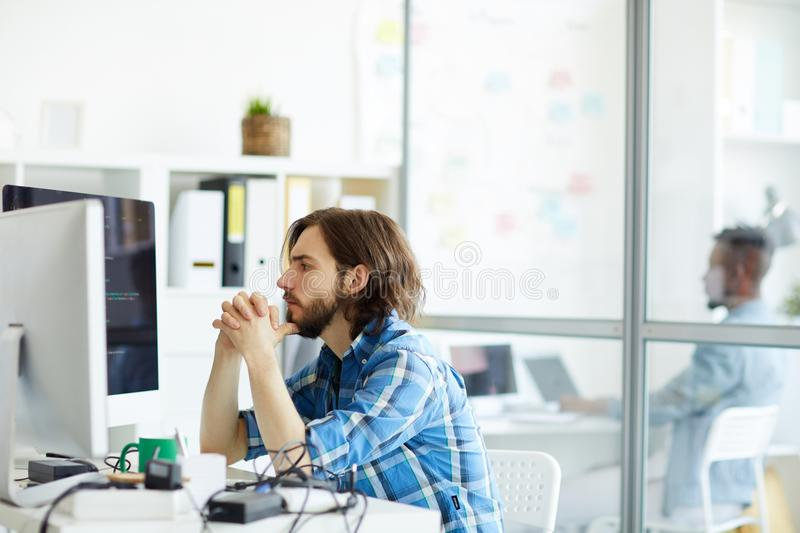 Young programmer. Serious it-manager concentrating on reading data on computer screen while sitting in office royalty free stock photography
