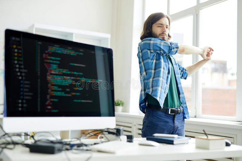 Relax for arms. Young programmer stretching his arms while keeping hands together during break for relax in office royalty free stock photography