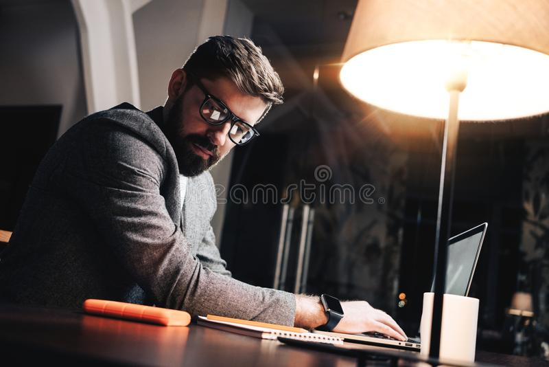 Young project manager looking on paper notepad and typing text on contemporary laptop royalty free stock images