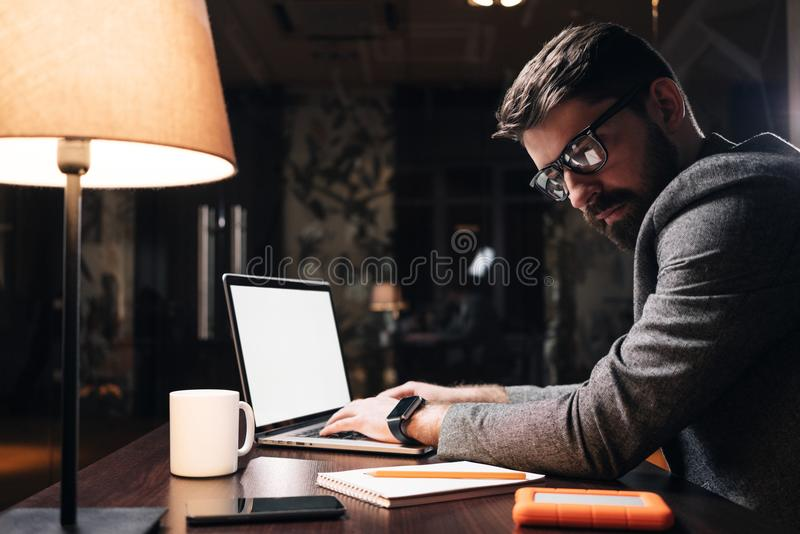 Young project manager typing text on laptop at night office. Bearded business man working on new startup in loft space royalty free stock image
