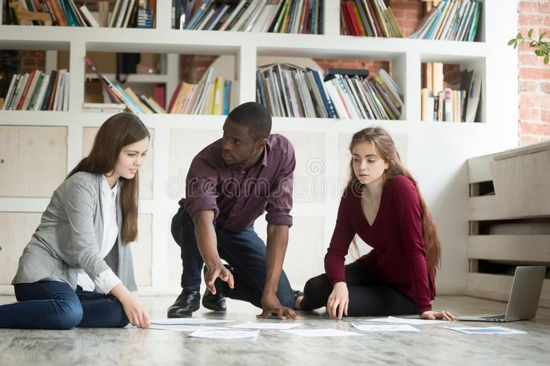 Young project team brainstorming working together on office floo. Young multi-ethnic project team brainstorming on office floor, african american leader teaching stock photos