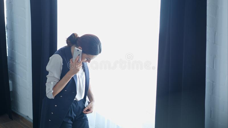 Young proud businesswoman is talking on her mobile phone with client, while standing near office window royalty free stock images