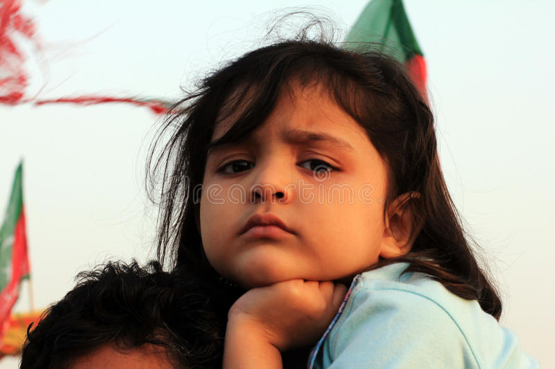 Young PTI Supporter in Karachi, Pakistan. A Young Supporters of PTI sits on her fathers shoulder in Karachi, Pakistan on 25th December 2011. Hundreds of royalty free stock photo