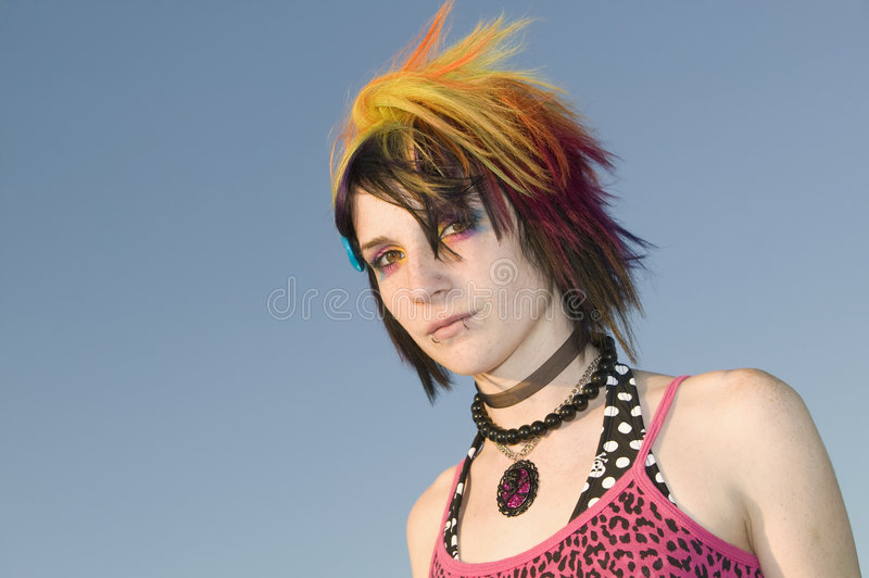 Young Punk Woman. Close-up of a young punk woman against a blue sky royalty free stock image