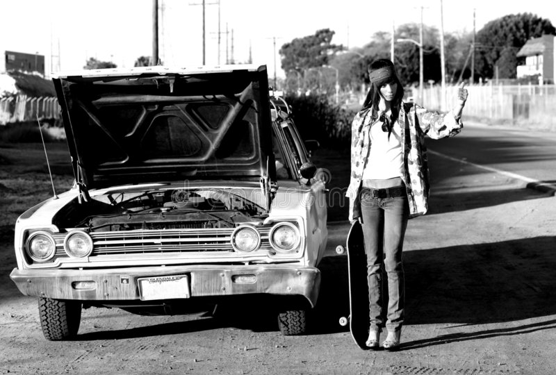 Young punk woman hitchhiking. Young, tall, brown-eyed woman having car problems royalty free stock photos
