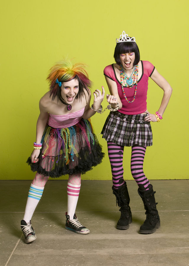 Young punk women linked by handcuffs. Young punk women in front of a green wall linked by handcuffs stock images