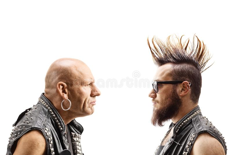 Young punker with a mohawk and an older bald punker looking at eachother. Isolated on white background royalty free stock images