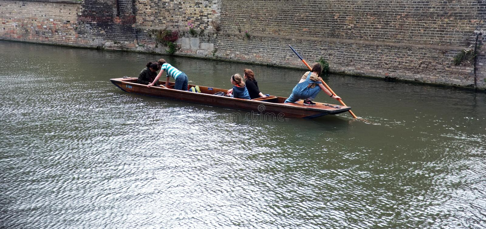 Young punter punting in Cambridge. Young punter punts the punt with her passengers in Cambridge,UK stock image