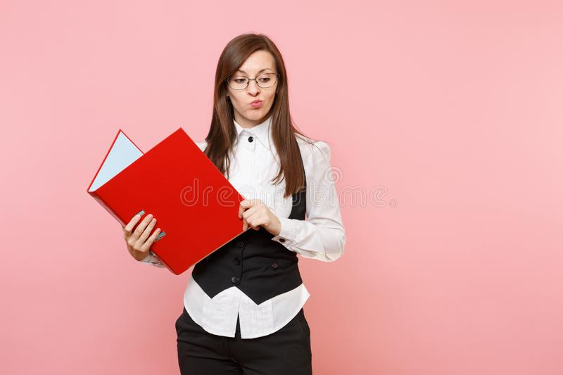 Young puzzled concerned business woman in glasses holding red folder for papers document looking down on pink. Background. Lady boss. Achievement career wealth royalty free stock image
