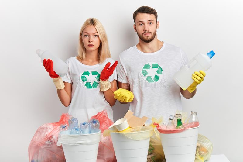 Young puzzled emotional couple doesn`t know what to do with litter. Serious puzzled emotional couple doesn`t know what to do with litter. Environmental pollution royalty free stock image