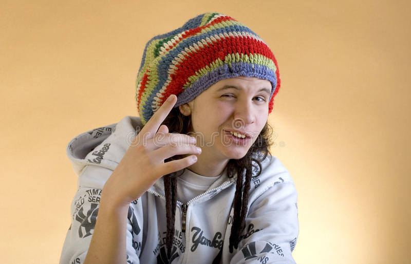 Young rapper showing thumbs. Studio photography on brown (orange) background stock photos