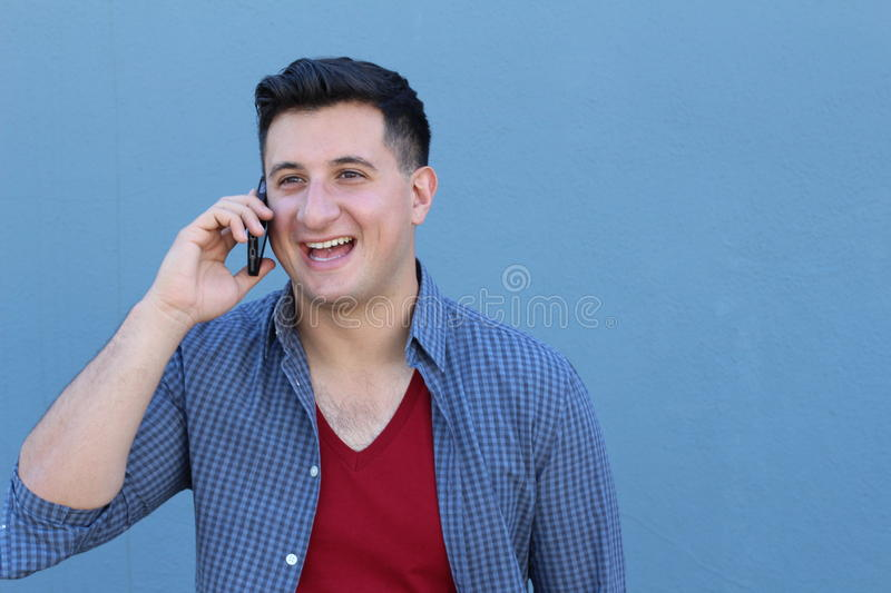 Young real looking natural man talking on his mobile phone to receive good news with copy space.  stock photography