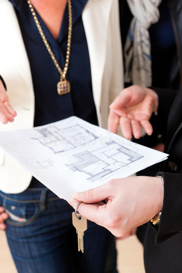 Young realtor explaining ground plan to couple. Young realtor explain ground plan to couple in an apartment stock images