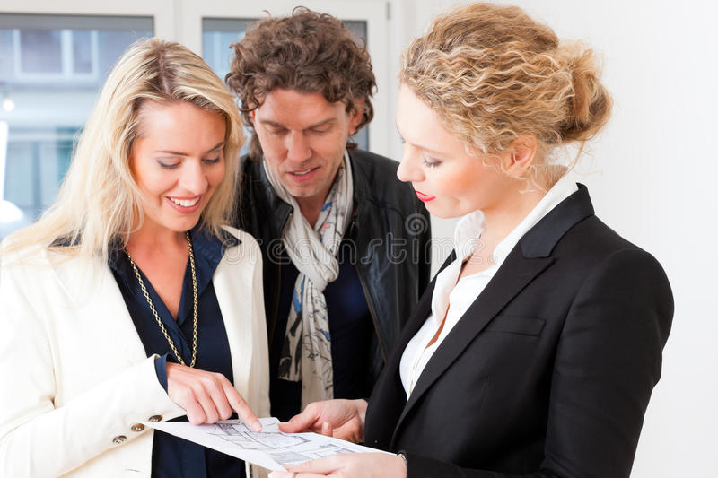 Young realtor explaining ground plan to couple royalty free stock photo