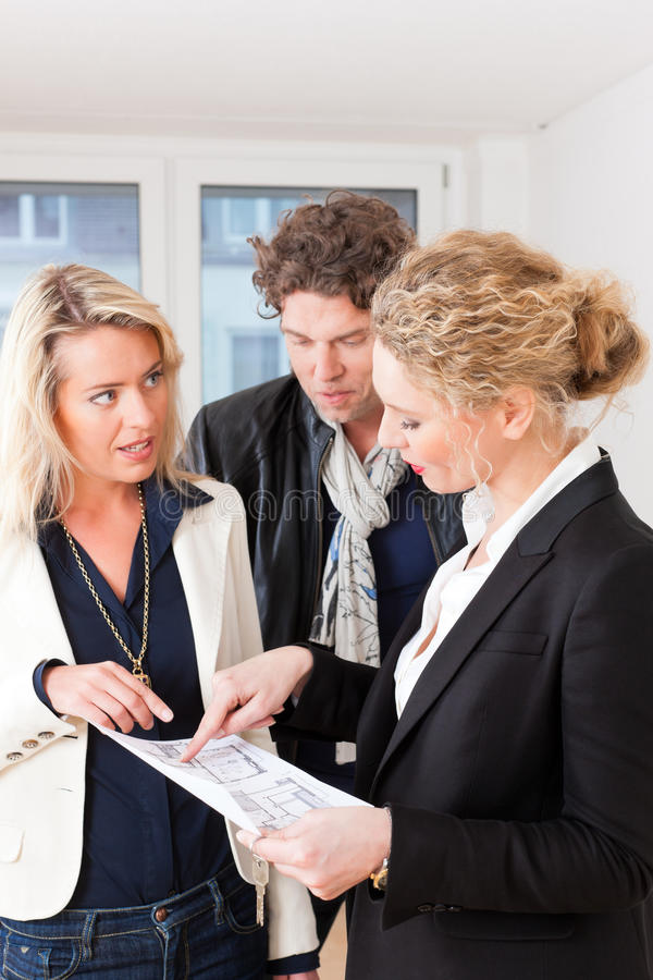 Young realtor explains lease agreement to couple. Young realtor explain lease agreement or purchase contract with floor layout to couple in an apartment, close stock photo