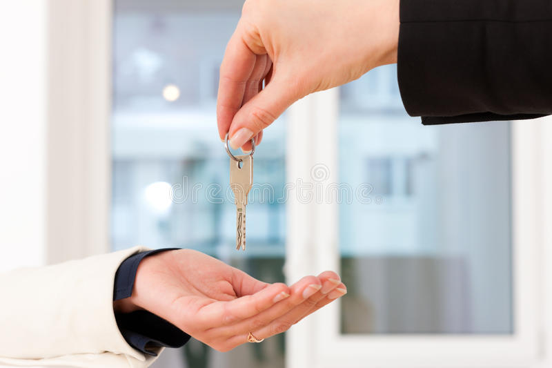 Young realtor is with keys in an apartment. Young realtor is giving the keys to an apartment to the tenant, close-up on keys and hands royalty free stock photography